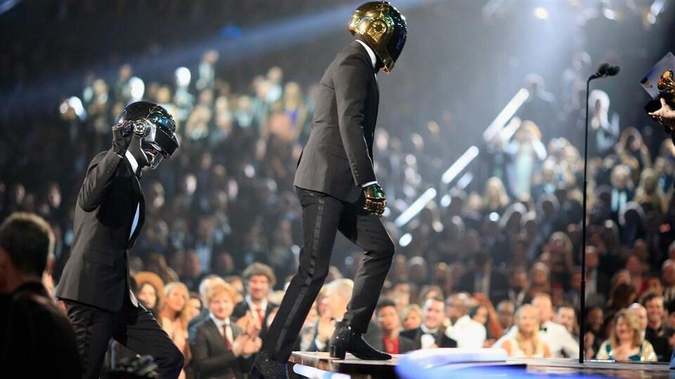 Les deux hommes montent sur la scène avec des casques intégraux, devant une foule.