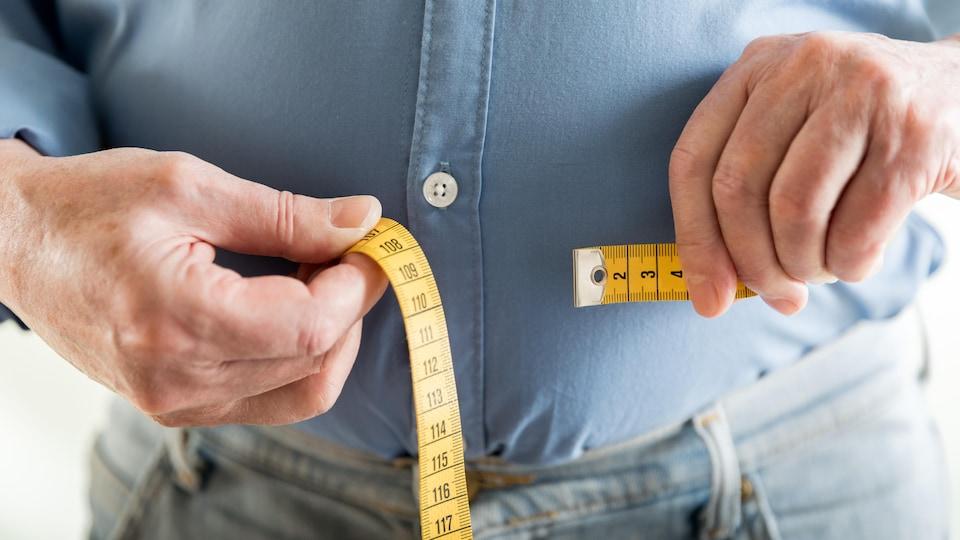 Gros plan sur les mains d'un homme qui mesure son tour de taille avec un ruban à mesurer.