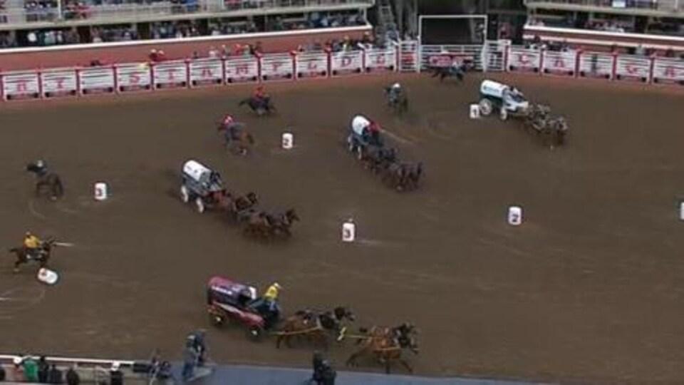 Un homme en jaune en bas de l'image est sur le point de tomber de son chariot. À côté de lui, on voit trois chariots conduits par des chevaux.