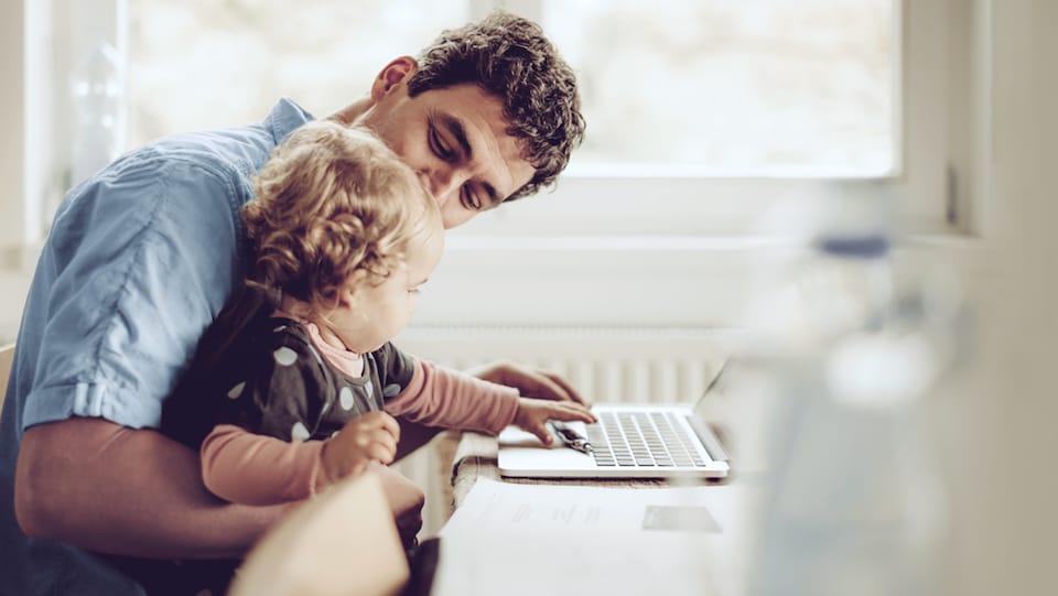 Photo d'un père assis à l'ordinateur avec son enfant dans les bras.