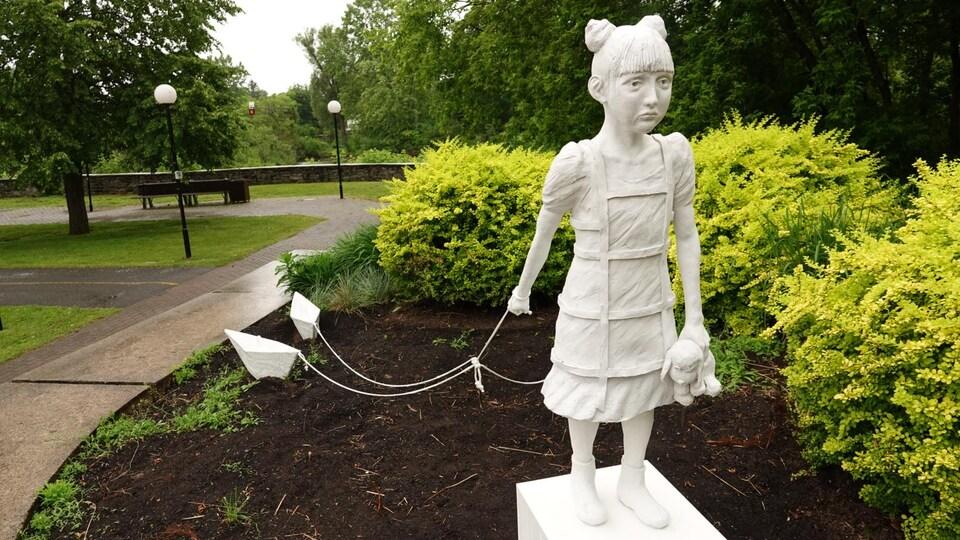 La sculpture blanche d'une fillette à l'air triste et tenant des bateaux au bout d'une corde est installée dans un jardin.