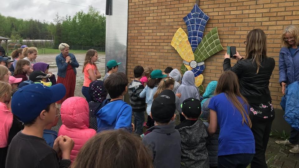 Des enfants et des membres du personnel d'une école assistent au dévoilement d'une oeuvre.