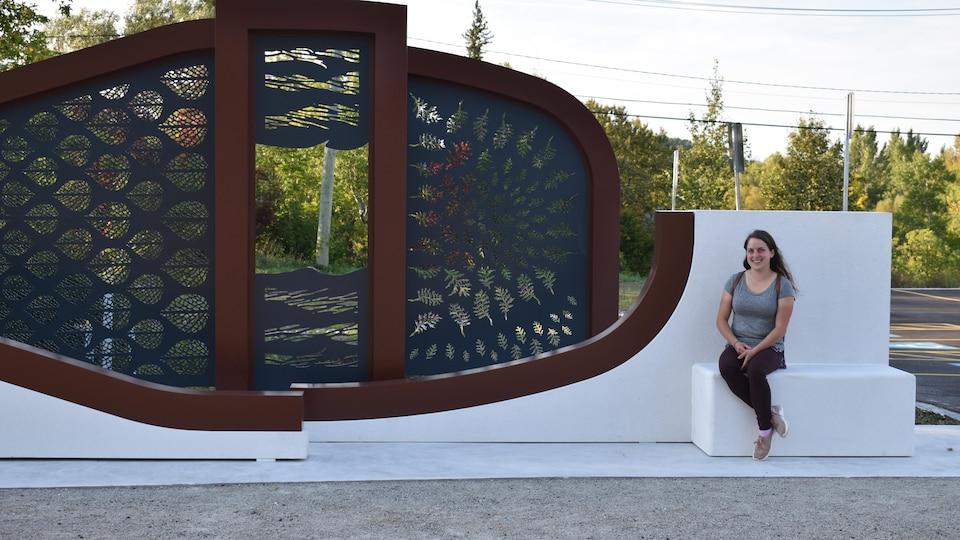 Des motifs de cèdre, de bouleau et de vague forment l'oeuvre de plusieurs sections. L'artiste Camille Rajotte est assise sur une partie de son oeuvre en forme de banc.