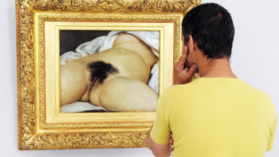 Un homme regarde le tableau L'Origine du monde