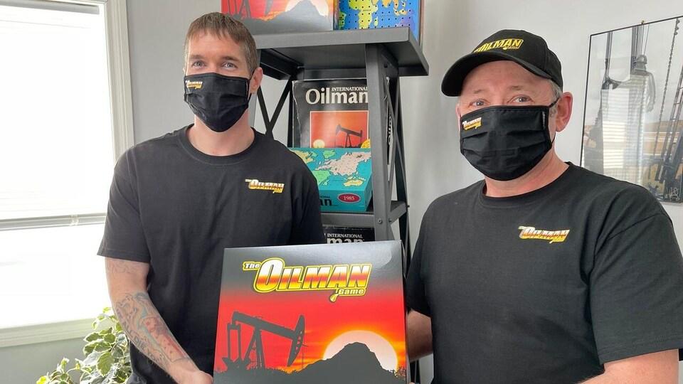 Deux hommes avec des masques portent un boîte du jeu de société The Oilman game.