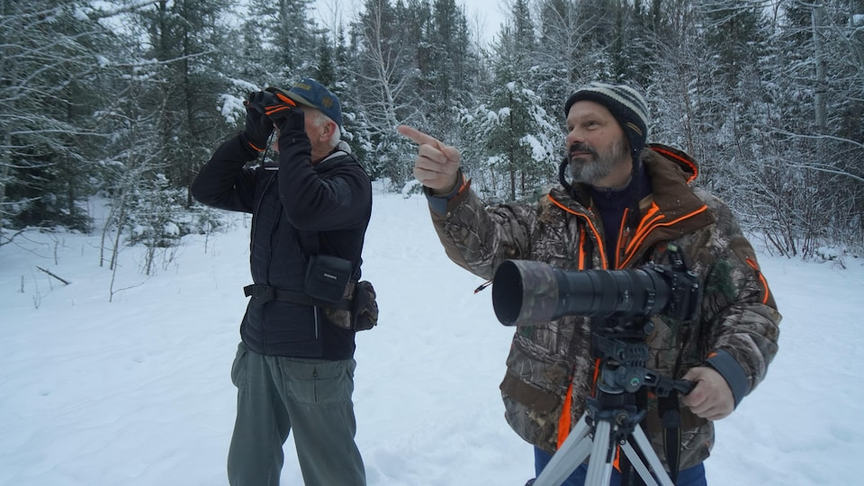 Deux hommes munis d'appareils photo et de longues-vues dans une forêt.