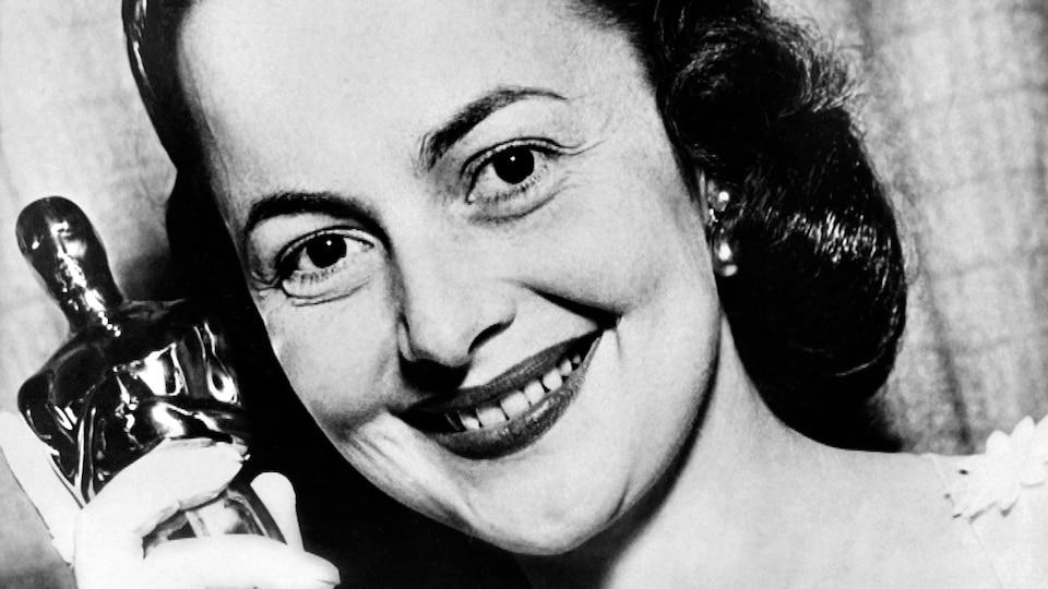 Une femme tient un Oscar dans ses mains.