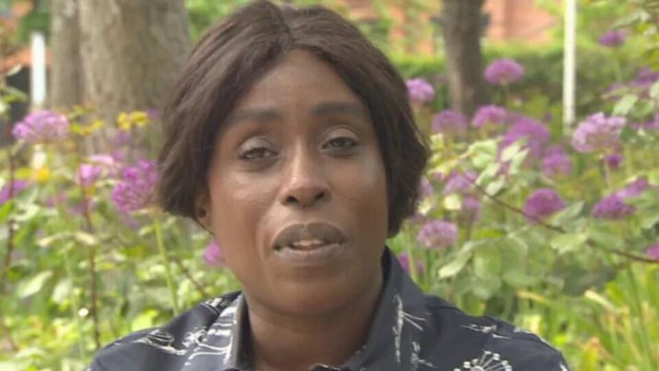 Olivia Nuamah, directrice générale de Pride Toronto est une femme noire, elle a les cheveux bruns, elle pose à l'extérieur, devant des fleurs violettes