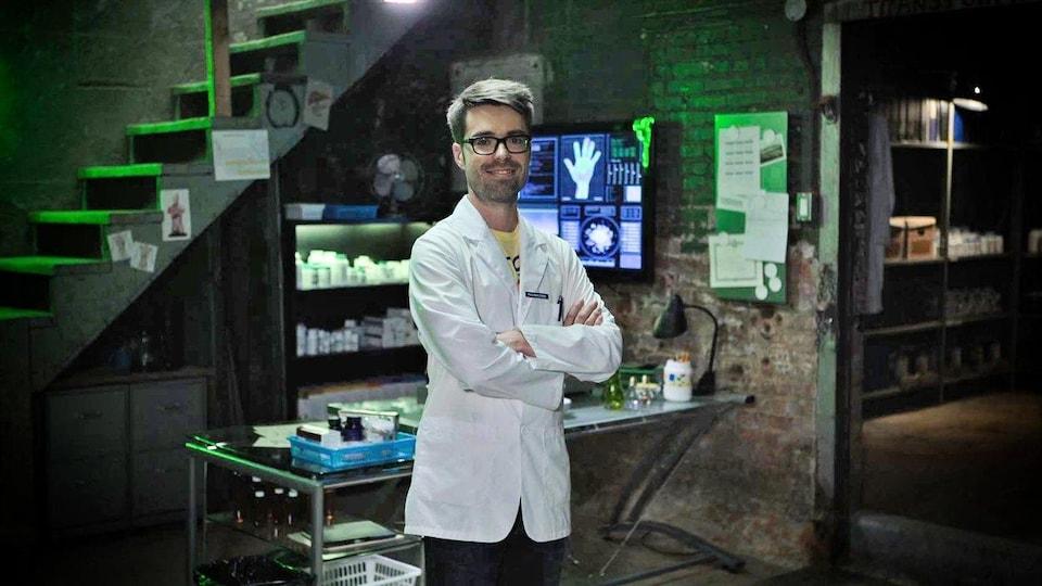Olivier Bernard, alias Le Pharmachien, pose en blouse blanche dans le laboratoire de son émission Les aventures du Pharmachien.