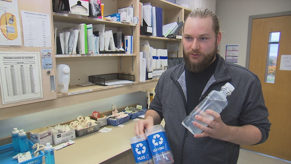 Un homme montre des bouteilles de plastique