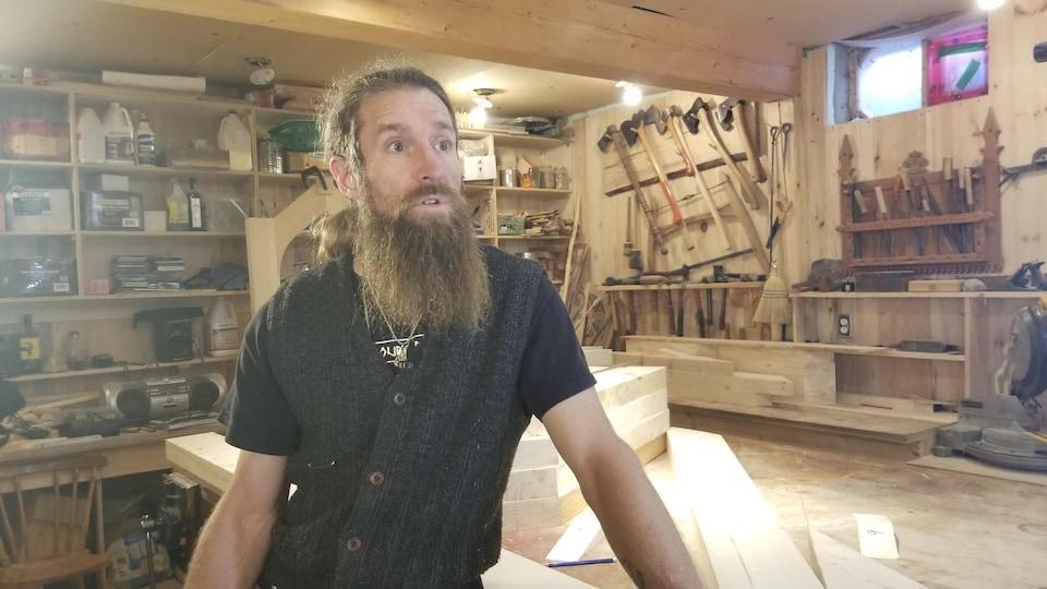 Un homme barbu se trouve dans un atelier de menuiserie.