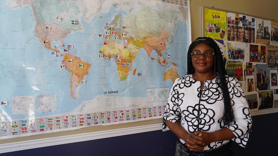 L'agente d'intégration au CAIDI, Aya Georgette Dje, pose devant une carte exposant l'ensemble des nationalités représentées en Beauce.