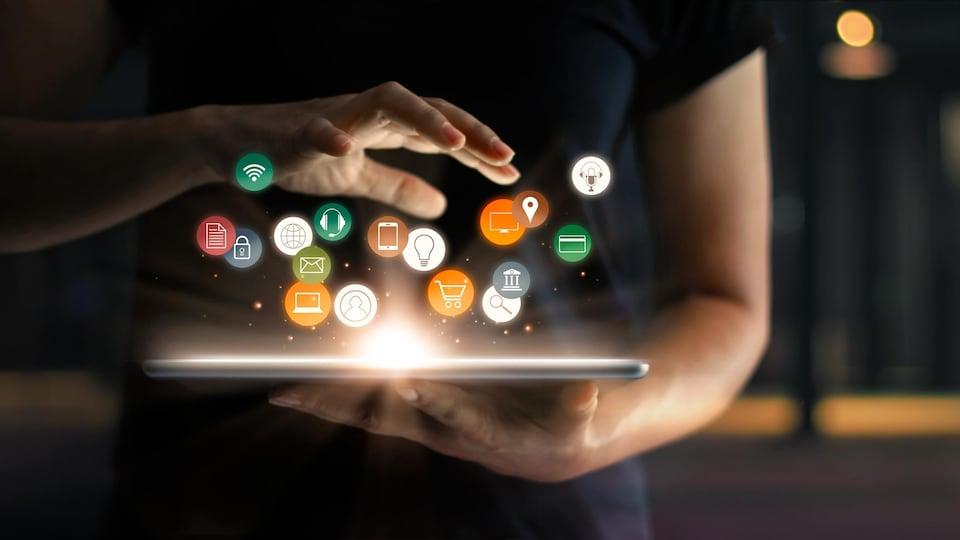Une personne tient une tablette avec plein de symboles d'applications qui flottent par-dessus.