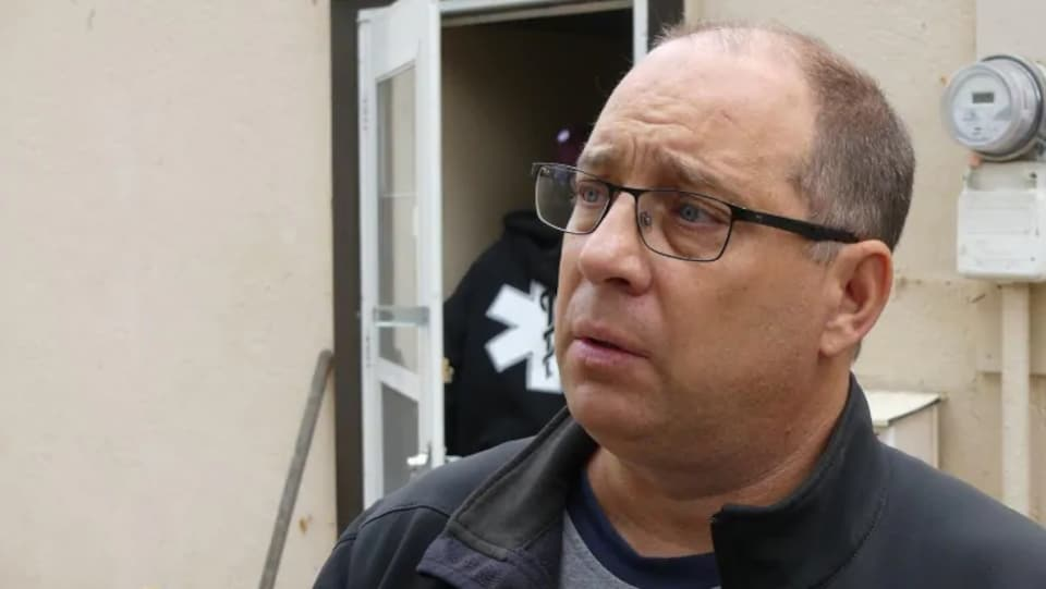 Un homme ayant l'air épuisé parle avec tristesse à un journaliste hors cadre. Il se tient devant le mur d'un bâtiment.