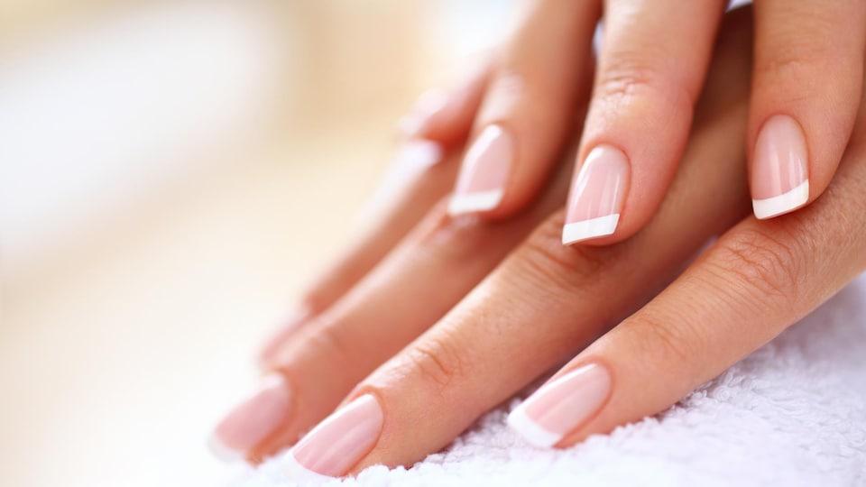 Un plan rapproché des mains d'une femme aux ongles manucurés.