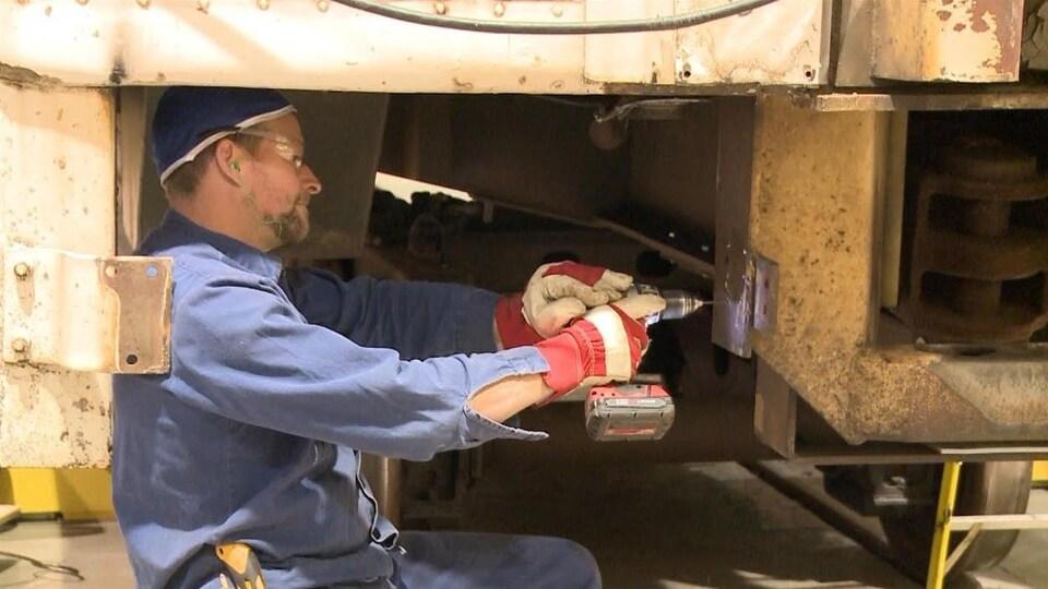 Un homme qui tient une perceuse et qui travaille à réparer un wagon de train.