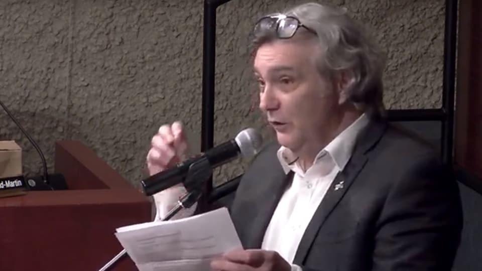 Le directeur de la Société St-Jean-Baptiste de Trois-Rivières, Guy Rousseau, au micro, dans la salle municipale du conseil de Trois-Rivières, avec une feuille à la main.