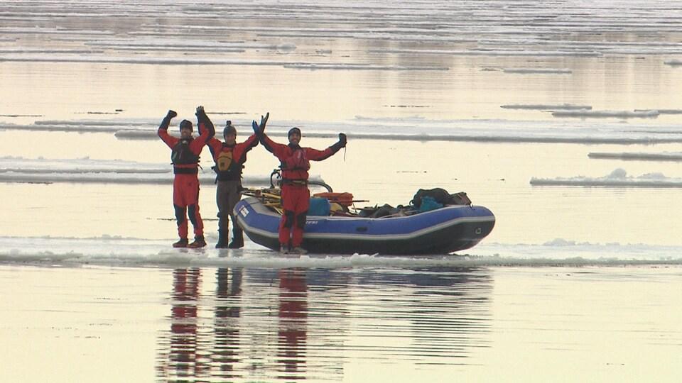 Trois hommes, les bras en l'air, prennent la pose à côté de leur canot pneumatique sur la banquise