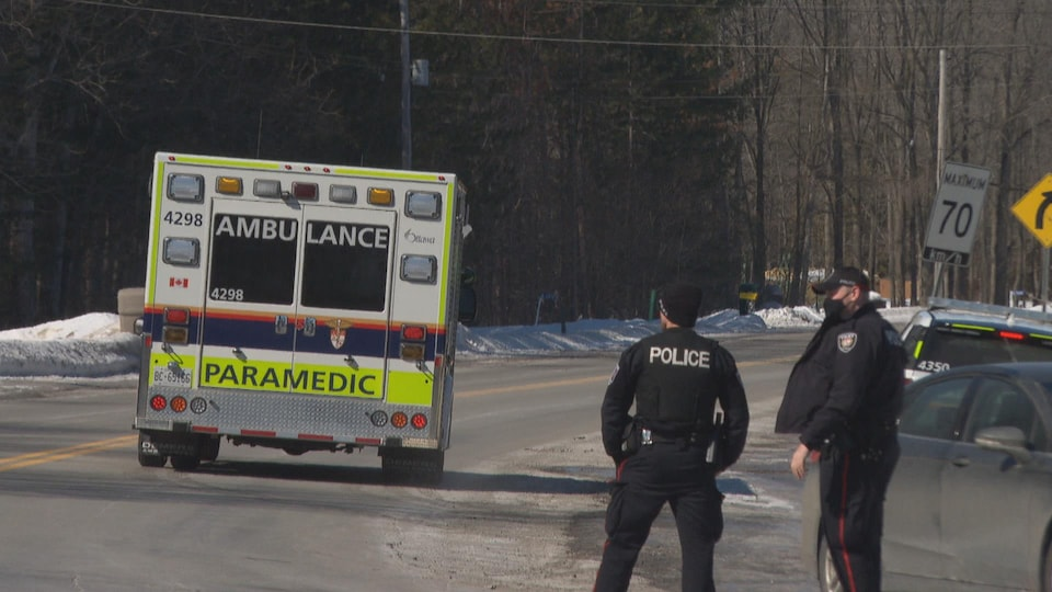 Deux policiers se tiennent l'un à côté de l'autre en bord de route pendant qu'une ambulance s'éloigne.