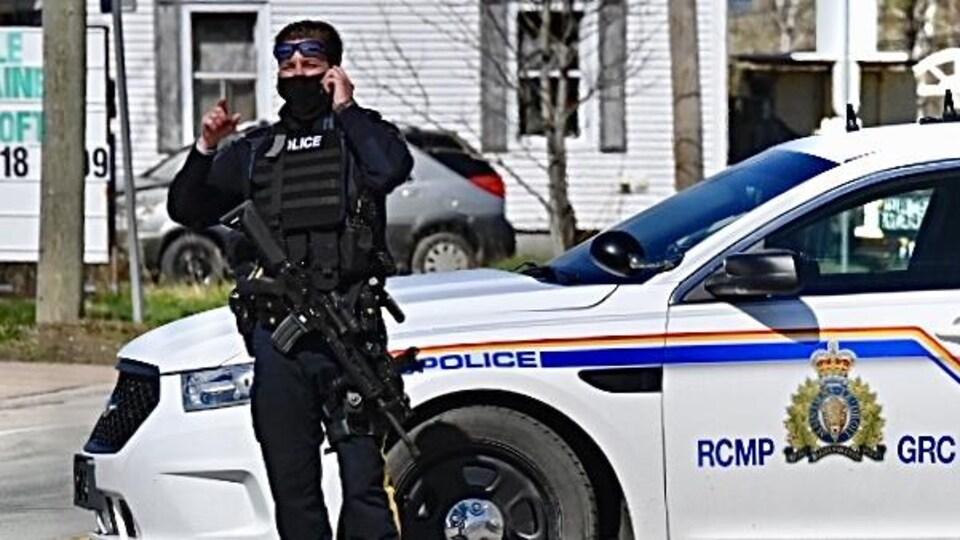 Un policier armé parle au téléphone.