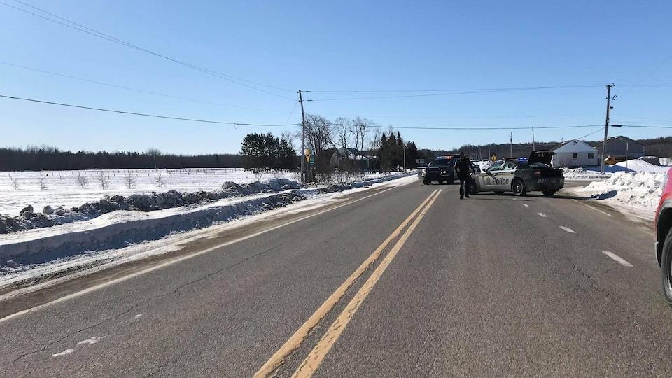Deux voitures de police sont arrêtées au milieu de la route.
