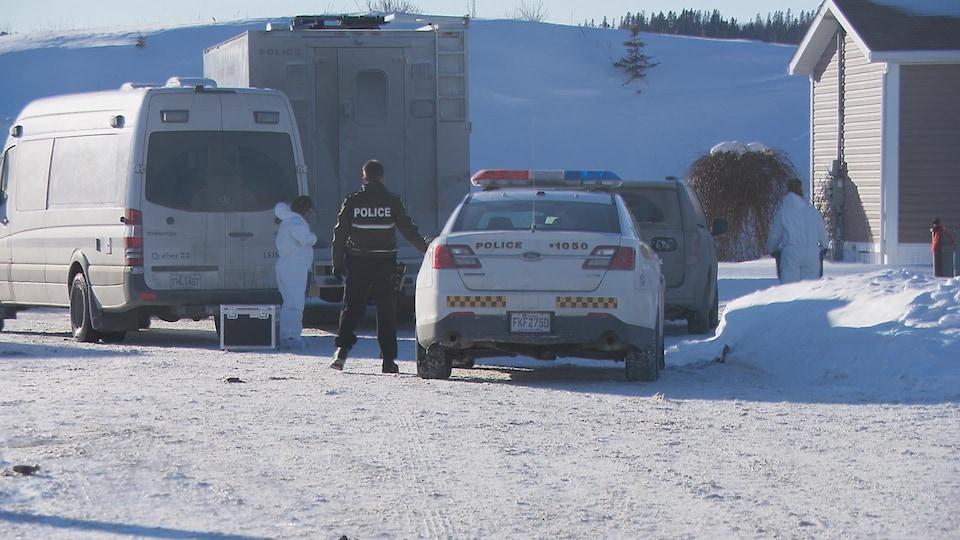 Des membres du corps policiers se préparent près des véhicules.