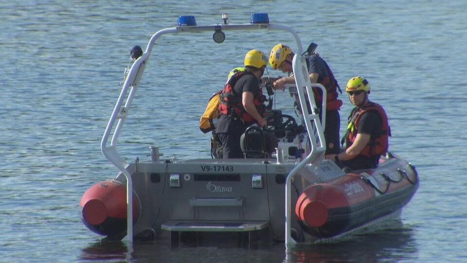 Un groupe d'intervenants d'une unité marine sont à bord d'une embarcation, sur la rivière des Outaouais.