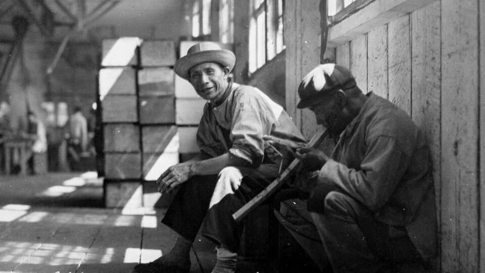 Un homme accroupi fume une pipe remplie d'opium