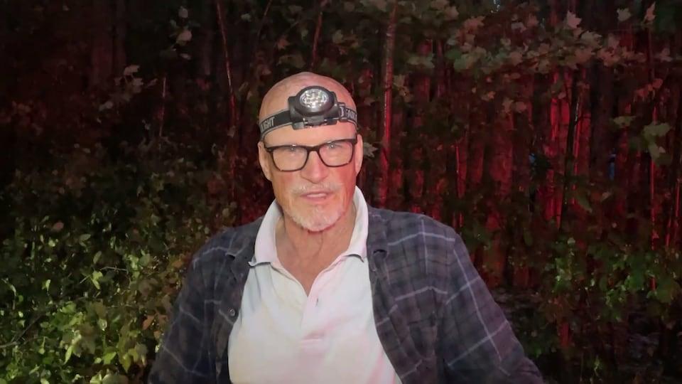 L'homme porte une lampe sur le front, alors qu'autour de lui règne la pénombre.