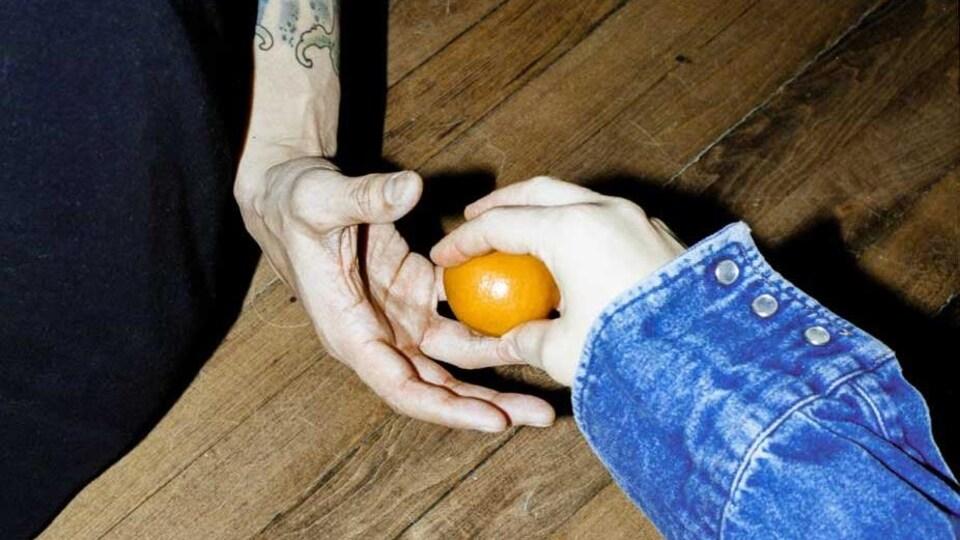 une personne passe une orange à une autre.