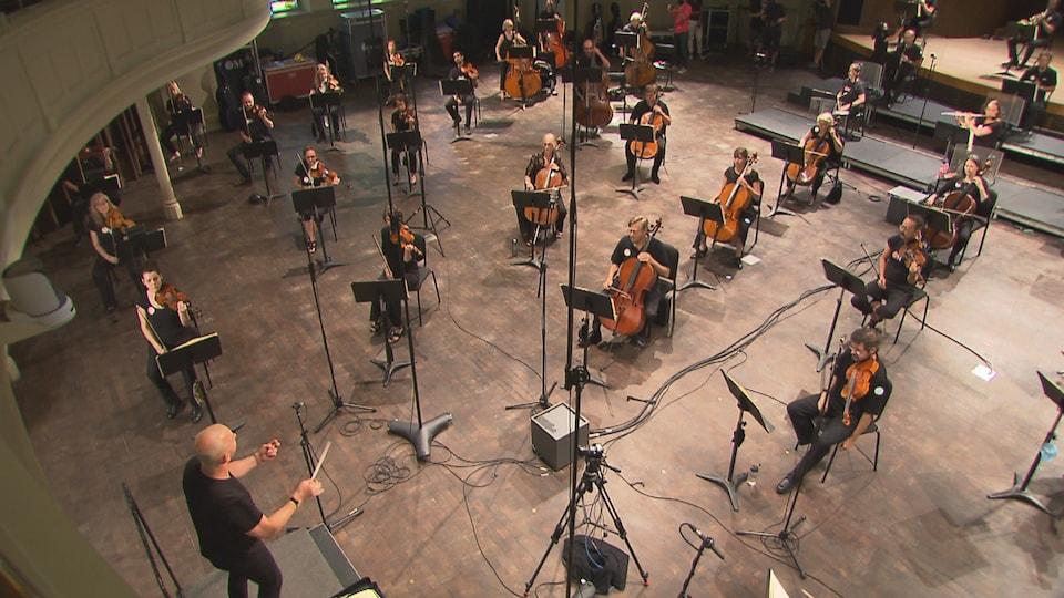 Yannick Nézet-Séguin dirige les musiciens de l'orchestre, placés à deux mètres les uns des autres.