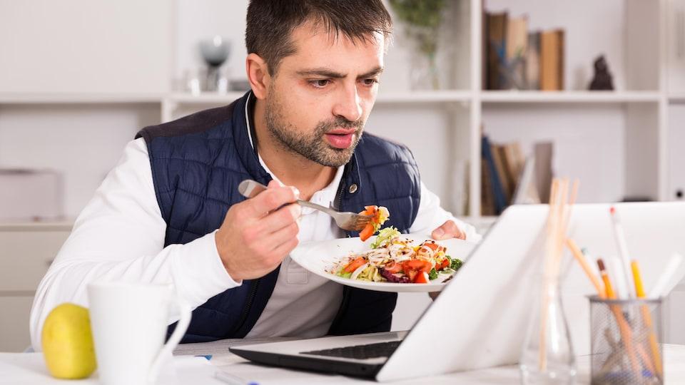 Un homme tient son assiette et mange devant son ordinateur portable.