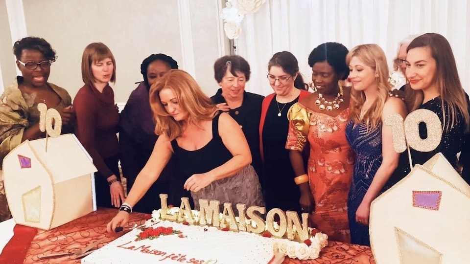 Une dizaine de femmes de l'organisme La Maison pose derrière un gâteau afin de célébrer les 10 ans du centre d'hébergement.