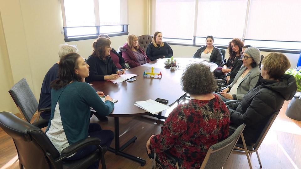 12 femmes assises autour d'une table avec un pont miniature en bois au centre de la table.