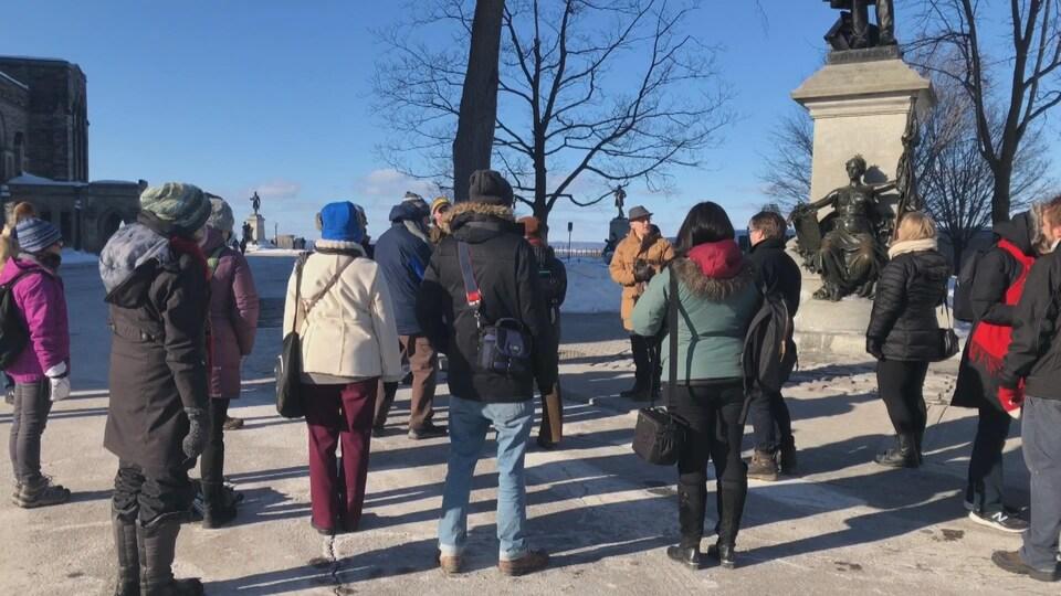 Des gens rassemblés devant une statue et des arbres.