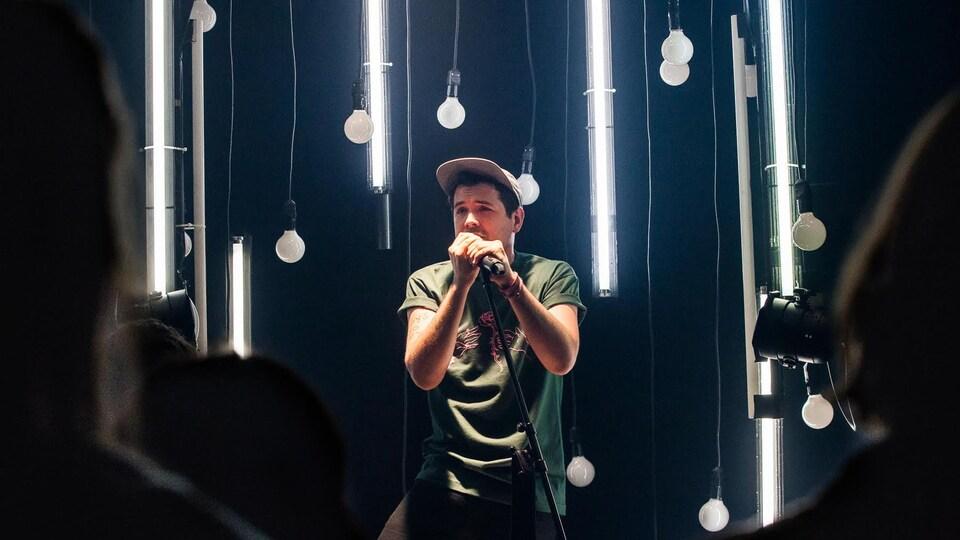 Un homme se tient debout devant des spectateurs vus de dos. Il tient un micro sur pied à deux mains et porte un t-shirt vert et une casquette. Il est entouré d'ampoules et de néons suspendus.