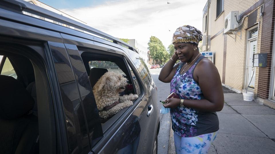 Osako Omba regarde son chien Lolita dans la fenêtre de sa voiture.