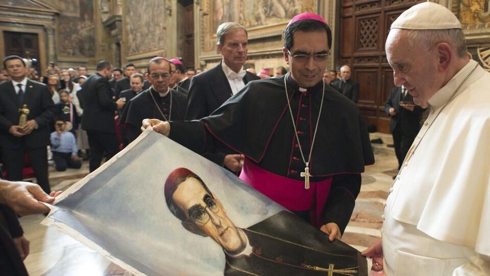 Le pape tient une photo d'Oscar Romero, qu'il regardre.