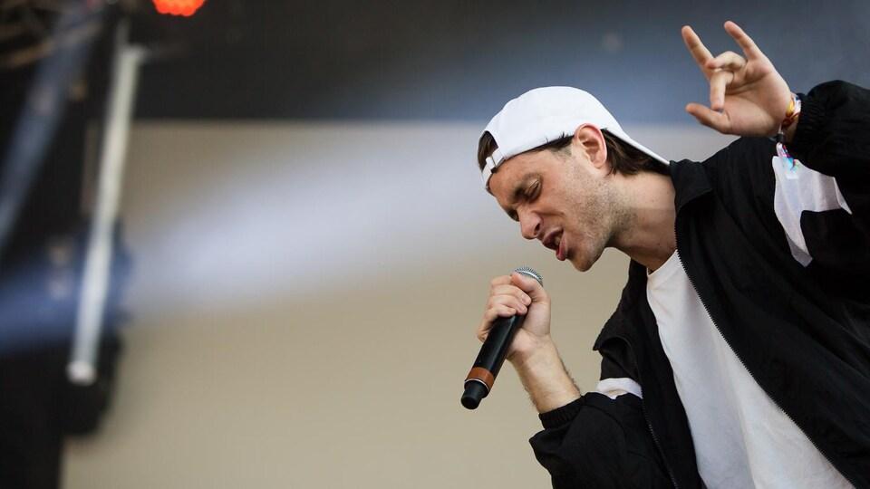 Le rappeur Loud pendant un concert, une main dans les airs.