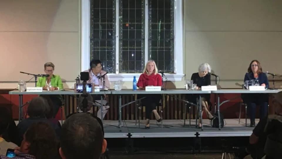 Cinq femmes derrière une table.