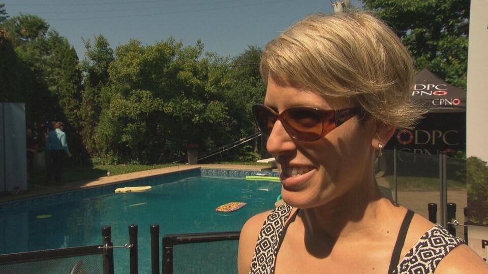 Une dame répond aux questions d'un journaliste devant sa piscine creusée.