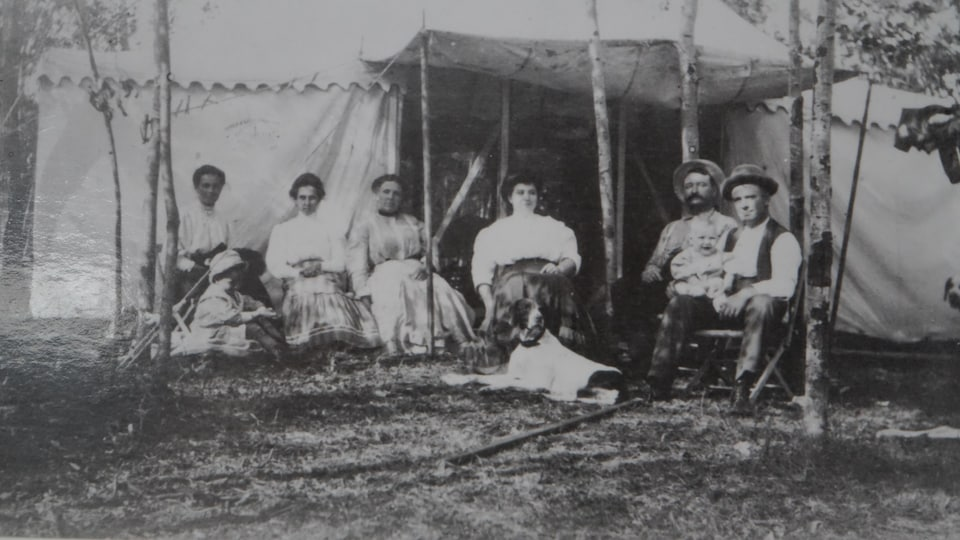 Des Canadiens français assis devant une tente, photo prise par Dann Mckenzie