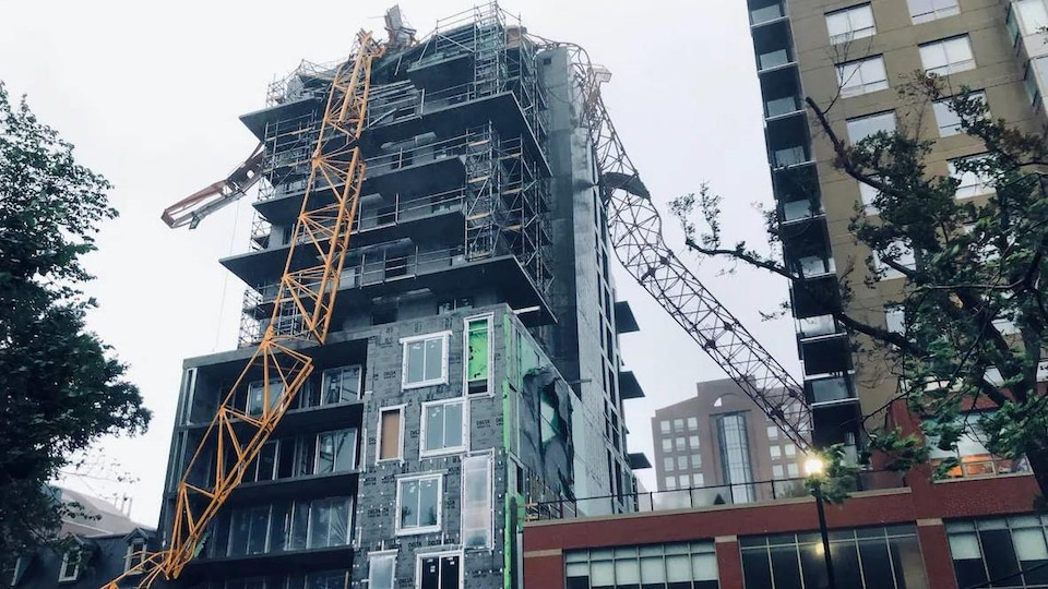 Grue jaune tombée sur le toit d'un immeuble en construction.
