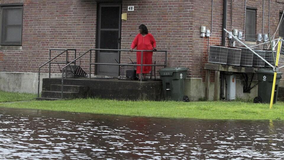 Une femme est postée sur sa galerie et regarde l'eau envahir le gazon.