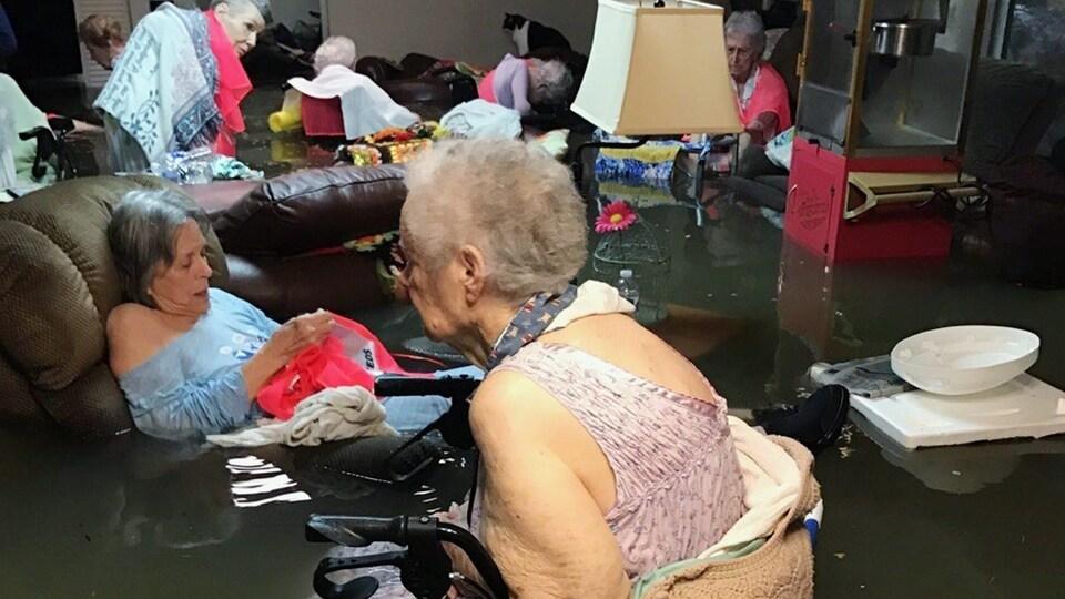 Des personnes âgées ont de l'eau jusqu'à la taille.