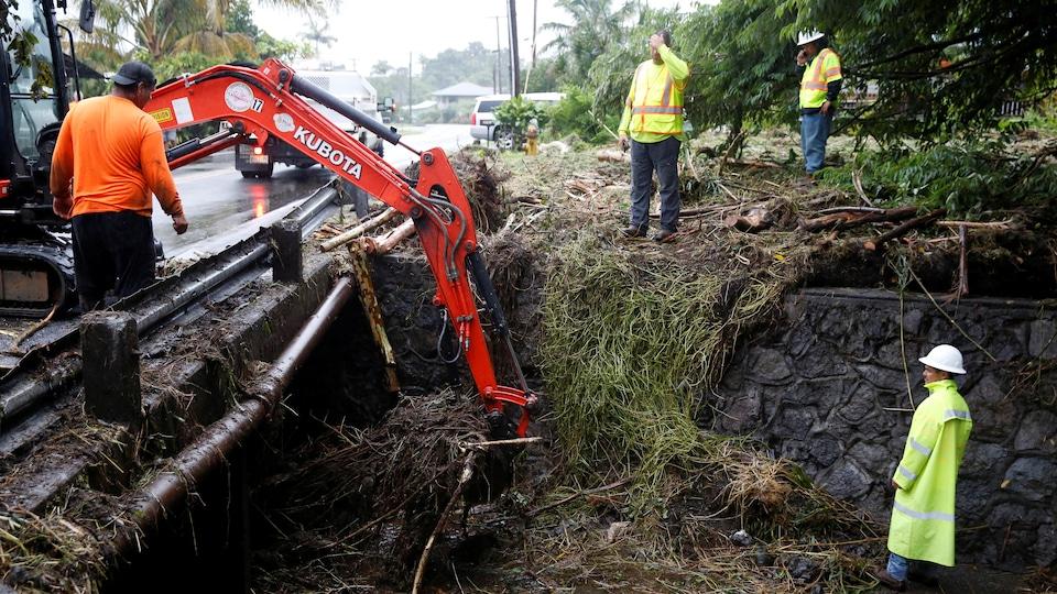 Une machine déblaie la route, encombrée par de la terre et des branches.