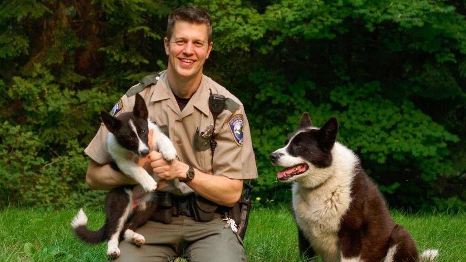 L'agent de conservation du WDFW Nick Jorg pose fièrement avec deux chiens d'ours de Carélie.