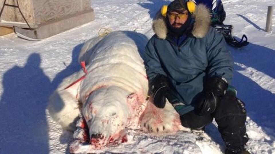 Le chasseur Darrell Voisey pose à côté de l'ours polaire qu'il a tué.