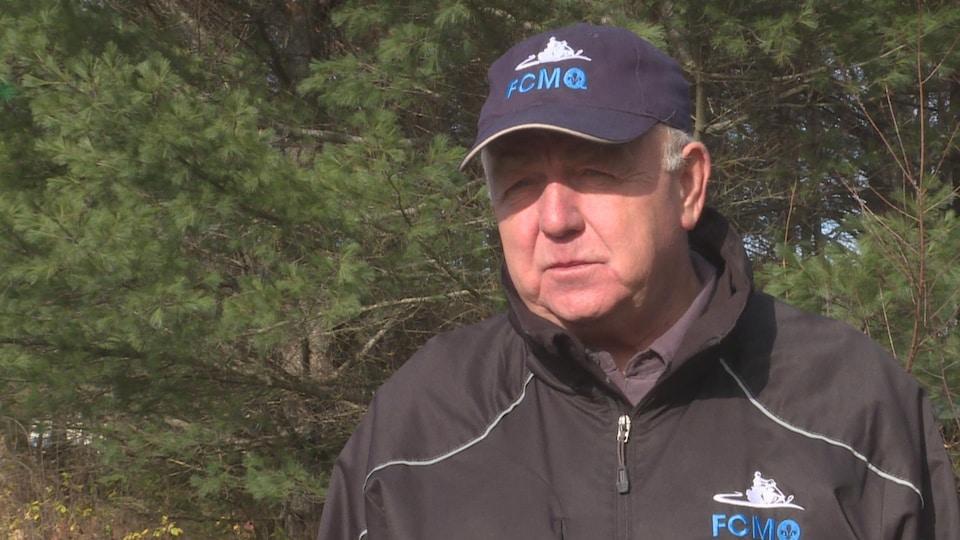 Pierre Tremblay en entrevue devant des arbres.