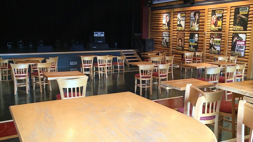 Des tables et des chaises d'une salle de spectacle ont été installées à deux mètres les unes des autres.